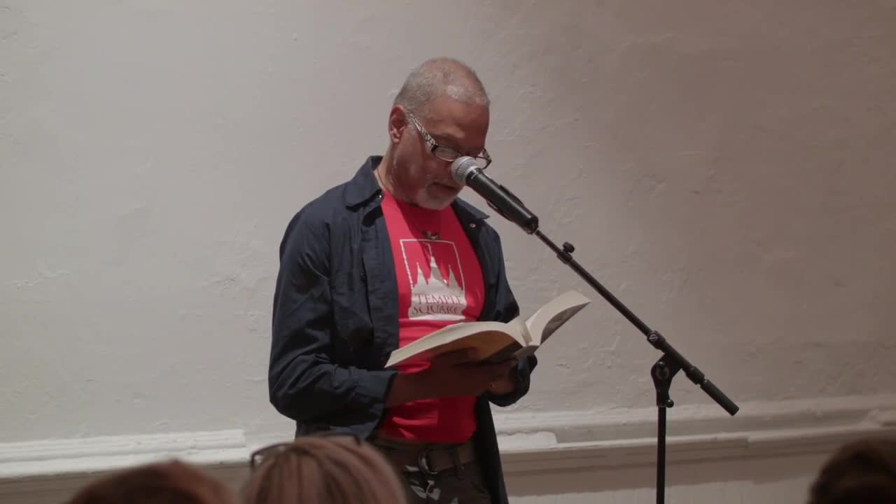 Two people read in front of a small audience
