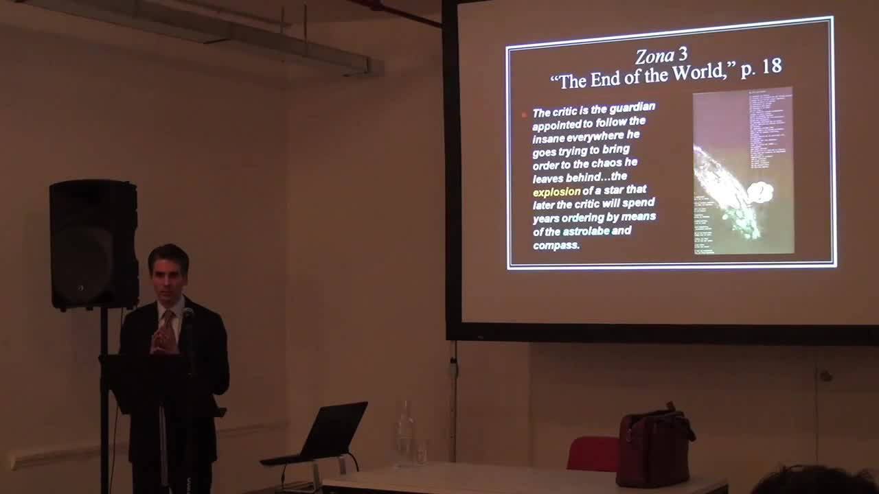 A man gives a talk in front of an image presentation projected on the screen behind him.